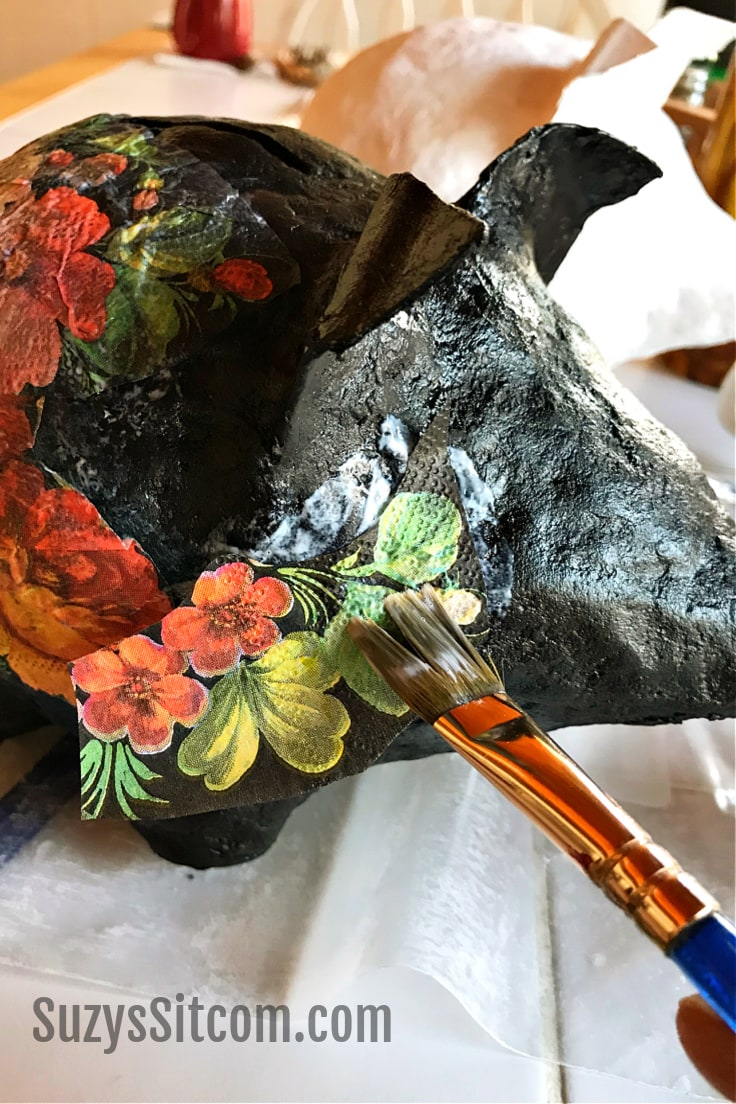 Using a paintbrush to add mod podge to floral napkins on the black pig.
