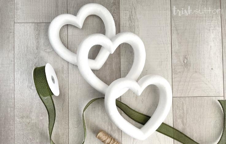 Three foam heart wreaths with green burlap ribbon and jute ribbon to create DIY decor.