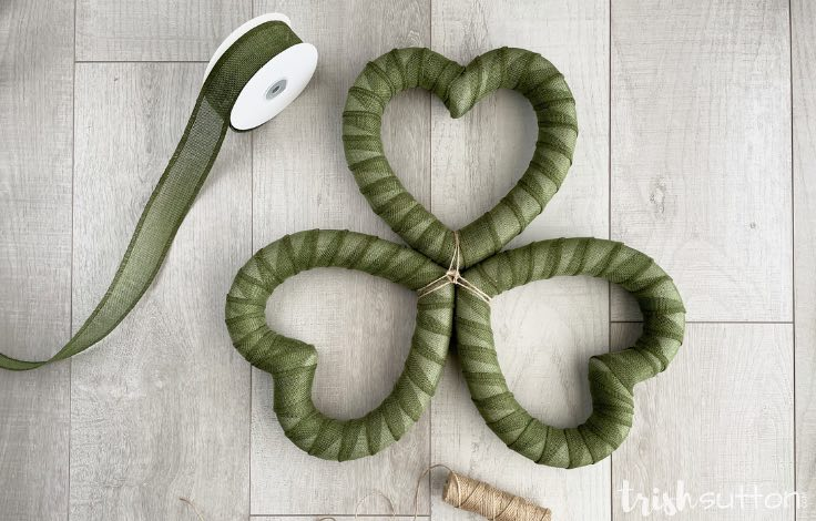 Three heart wreaths covered in green burlap ribbon in the shape of a shamrock on a wood background.