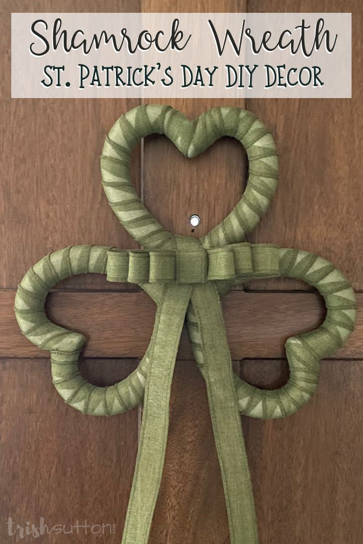 Green shamrock wreath with a bow hanging on a brown wood door.