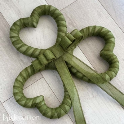 Green Shamrock Wreath layed out on a wood background.