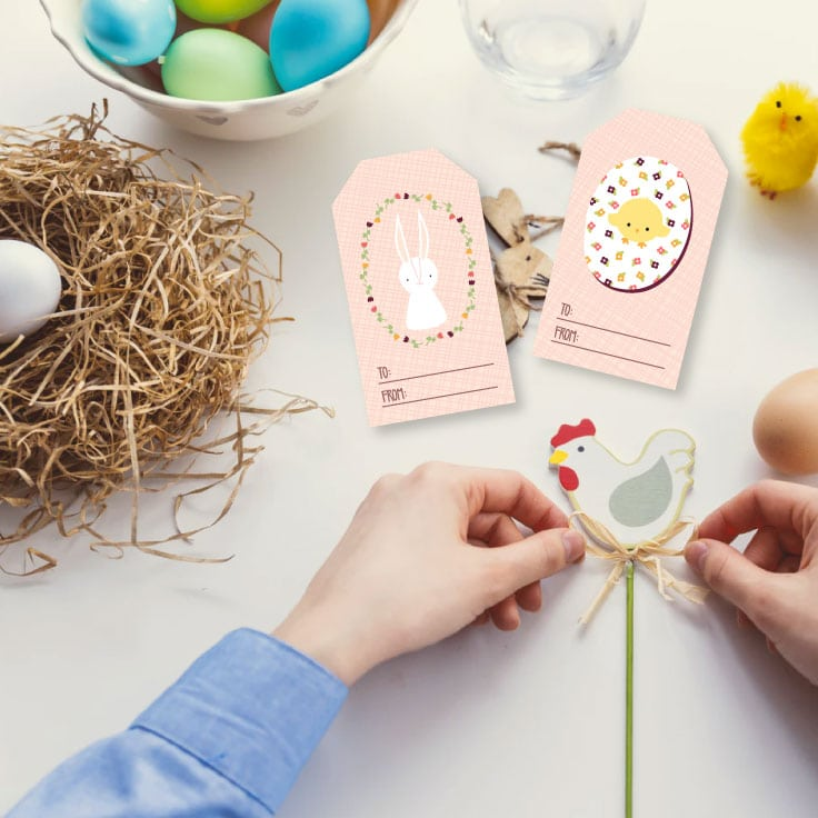 Preview of two decorative tag designs with a bunny and a chick, on a tabletop with Easter eggs, a paper nest with white egg, wooden rabbit decoration, glass of water, chick decoration and a person's hands tying ribbon on a wooden chicken decoration.