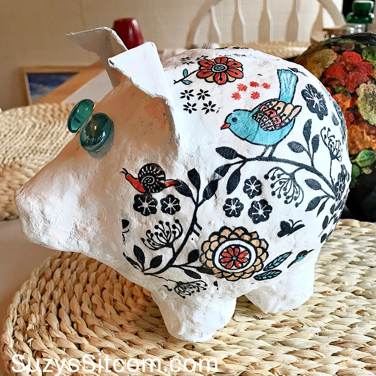 Finished white pig bank with floral and bird pattern on body and marble eyes.