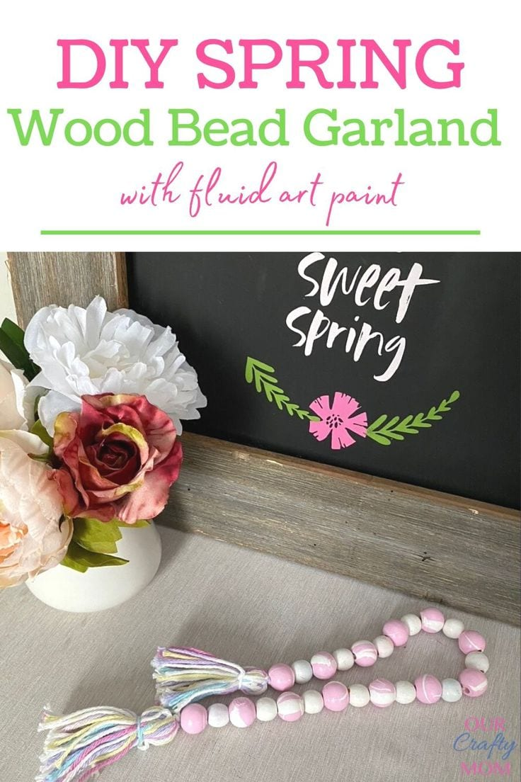 Pink and white marbled DIY spring wood bead garland with yarn tassels.