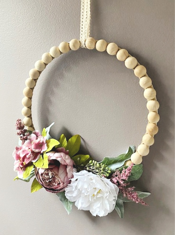 Wood bead hoop wreath with pink and white flowers from Our Crafty Mom.