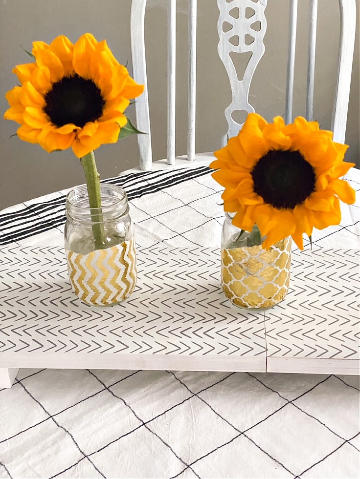 2 mason jars with gold embellishments in stripes and quatrefoil patterns.