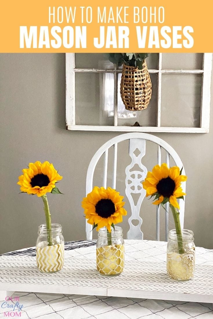 Gold painted mason jar flower vases on white table with sunflowers in them.