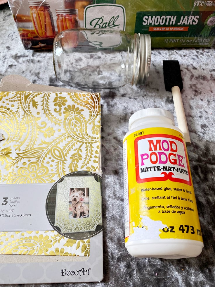 Package of decoupage paper, a mason jar, a sponge brush, and a bottle of Mod Podge.