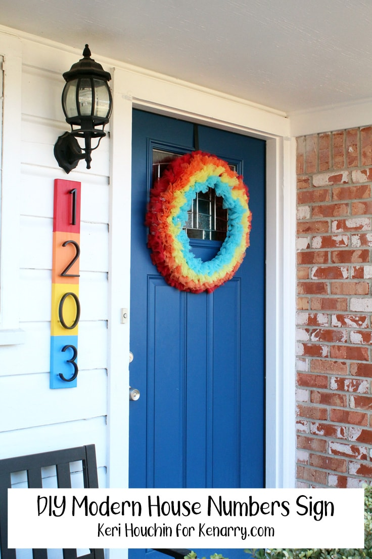 Front porch with a rainbow wreath on a blue door and a rainbow striped house numbers sign with text overlay