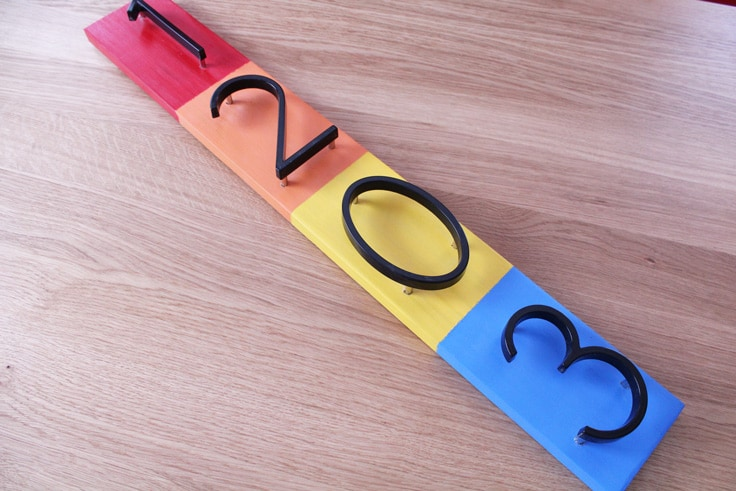 Board painted in red, orange, yellow, and blue with floating metal numbers 1, 2, 0, and 3.