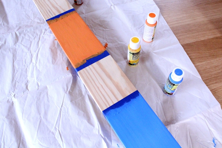 Wooden board divided with tape and painted in orange and blue.