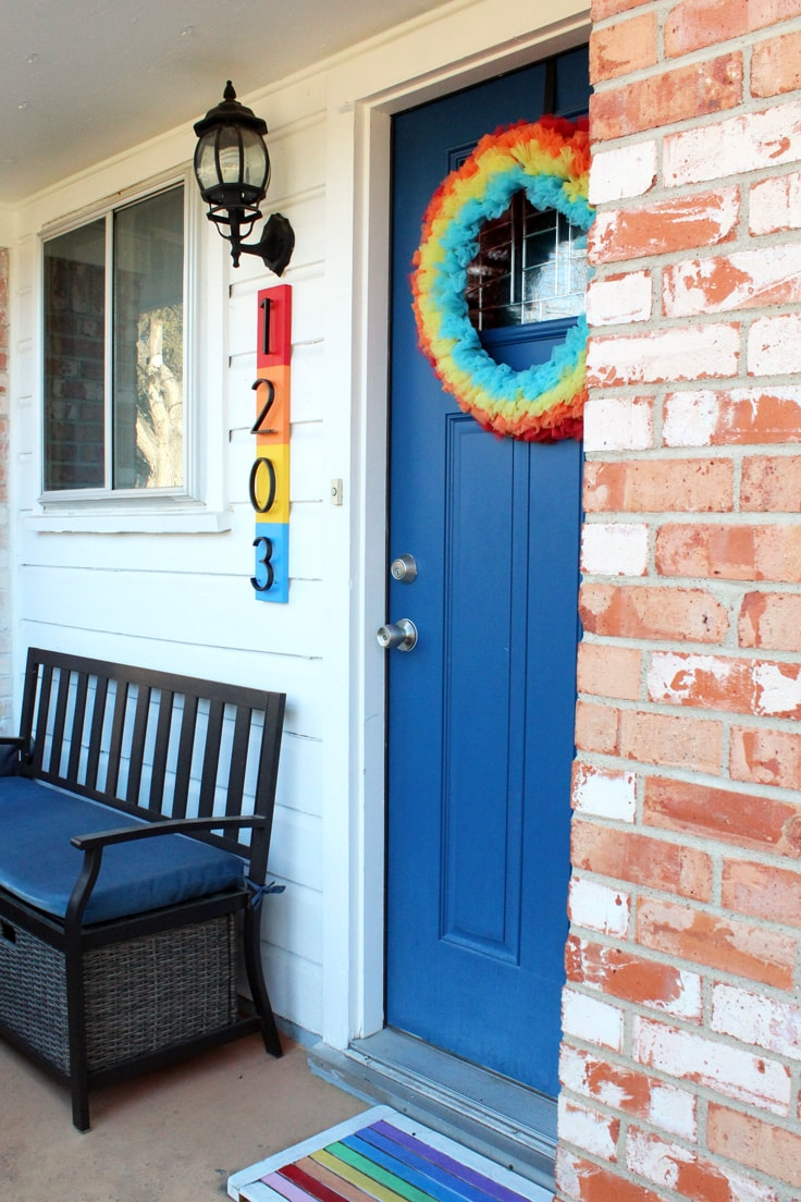 Rainbow house numbers beside a door.