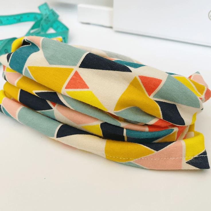 Fabric neck gaiter in bright triangle print fabric.