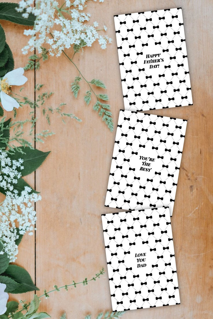 Preview of three bow-tie inspired Father's day card designs on a wooden table with white flowers and greenery decoration to the left.