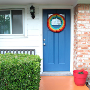 Colorful front porch with orange concrete, blue door, and rainbow wreath from One Mama's Daily Drama.