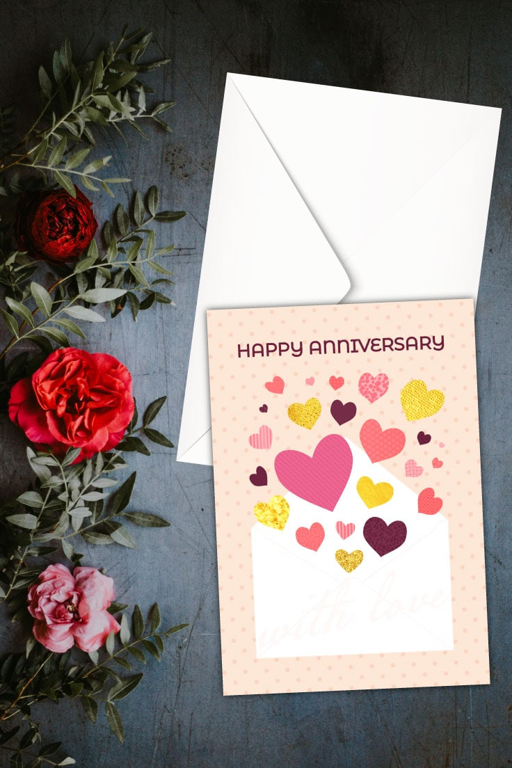 Preview of anniversary printable card on top of a white envelope with red and pink flowers and green foilage on the left.