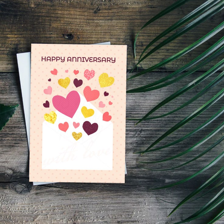A printable card design of hearts coming our of an envelope on wooden table with green fern leaves.