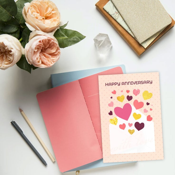 Preview of anniversary card printable on desk with notebooks, writing utensils, creme flowers and a clear crystal decoration.
