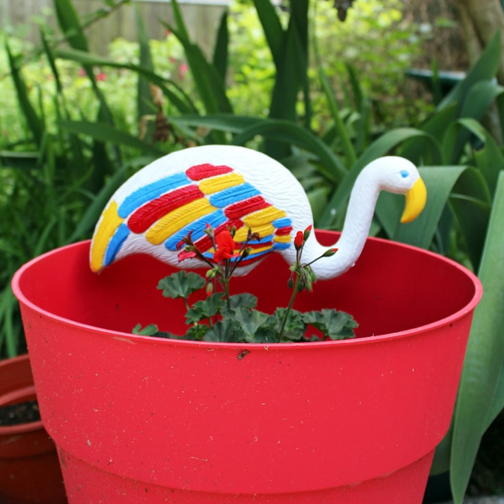 DIY painted yard flamingo in a planter from One Mama's Daily Drama.