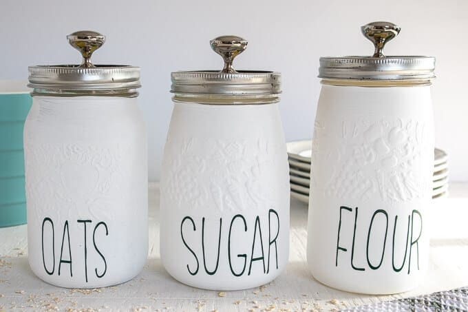 White kitchen canisters with Rae Dunn labels for