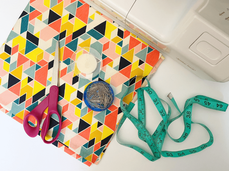 Colorful triangle print fabric, scissors, a fabric tape measure, and pins sitting beside a sewing machine.