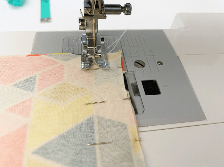 Closeup of a sewing machine stitching down a length of fabric.