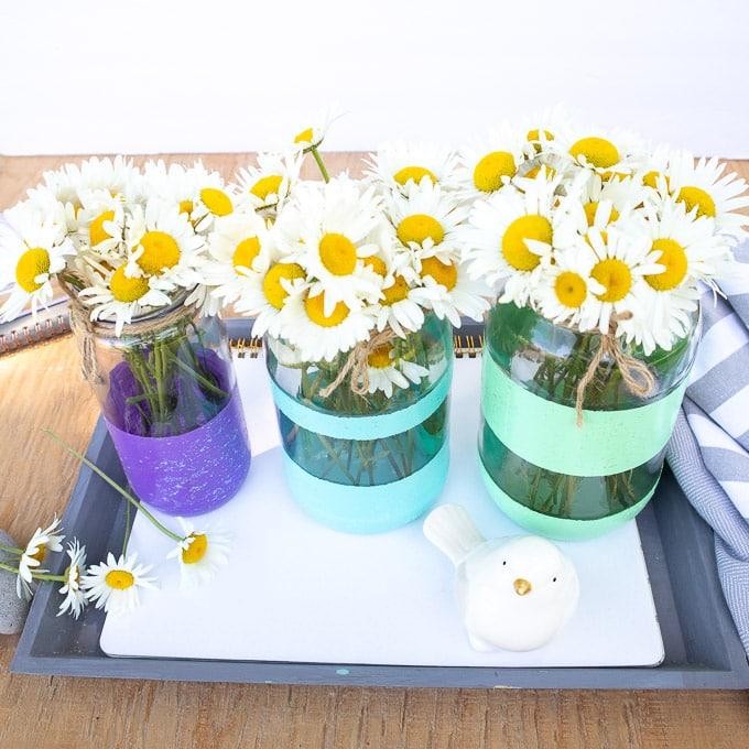 Glitter painted mason jar vases full of daisies.