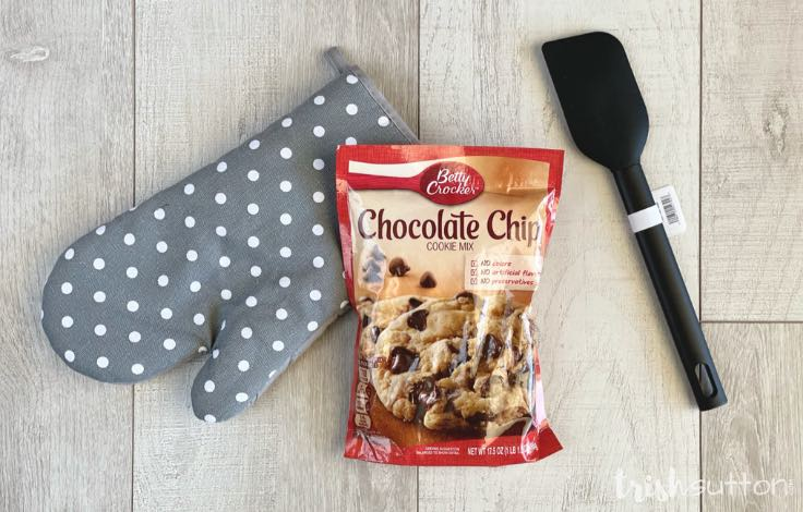 Oven mitt, cookie mix and spatula ready to gift a teacher on a wood background.
