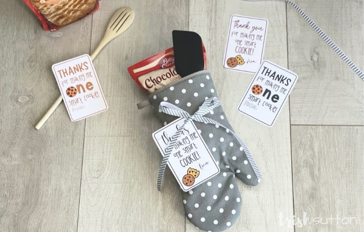 Teacher appreciation gift of oven mitt, cookie mix and spatula with four different gift tags on a wood background.