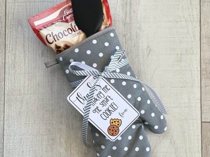 Teacher gift of oven mitt with cookie mix and spatula on a wood background.