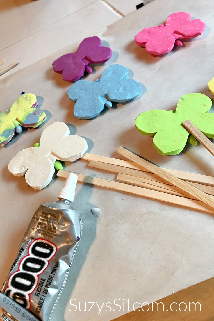 Gluing wooden craft sticks to the back of each butterfly.