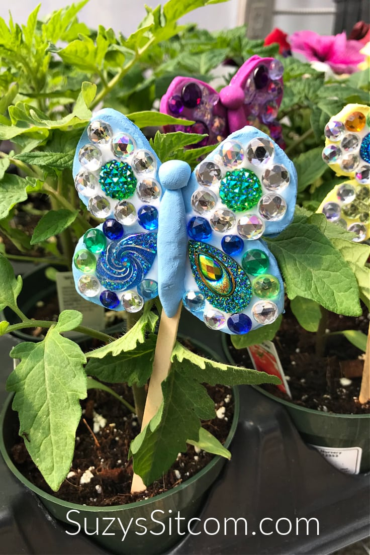 Blue, yellow, and purple clay butterfly pokes covered in sparkly gemstones.