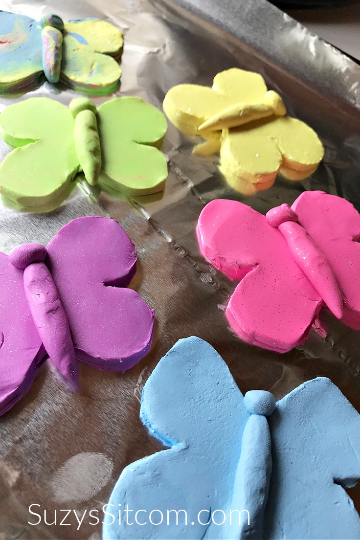 Blue, pink, purple, and yellow clay butterflies on a baking sheet.