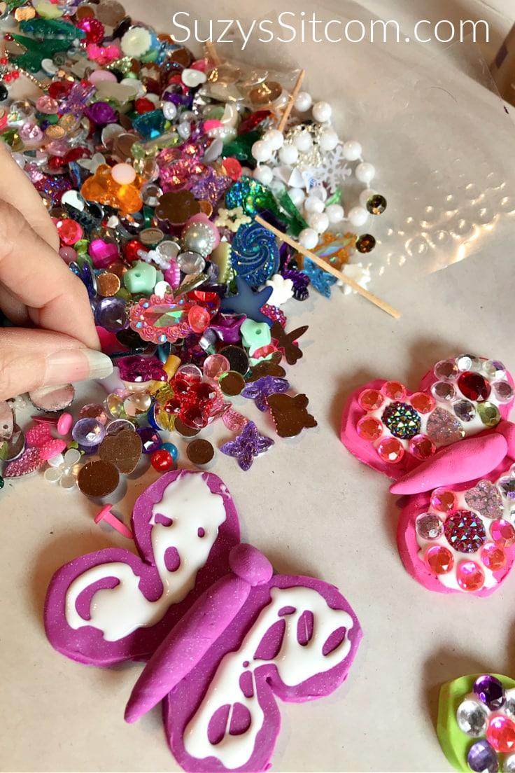 Gluing assorted gemstones onto the baked butterflies.