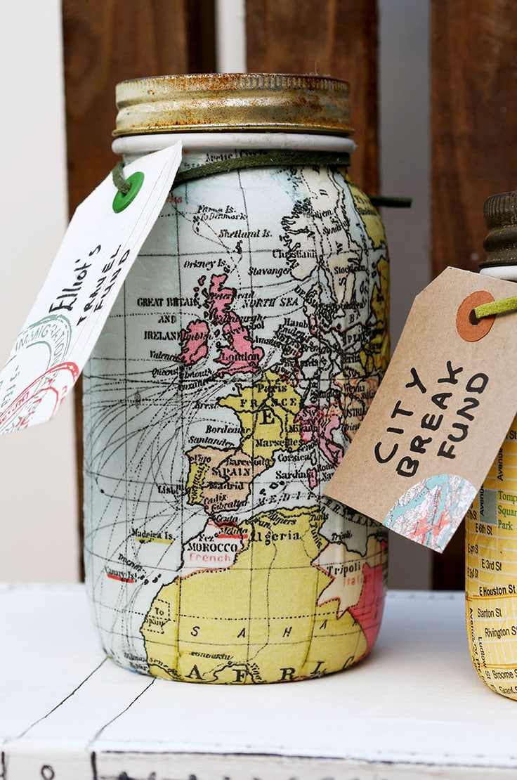 Glass jar bank covered in paper maps.
