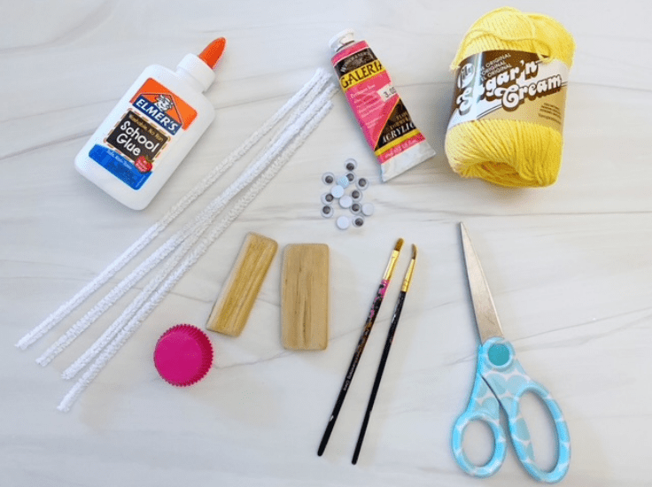 glue, pipe cleaners, yarn, paint, and paintbrushes - supplies to make a ballerina craft