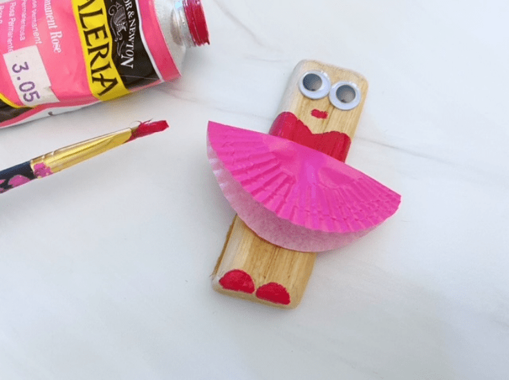 Painting the mouth and feet on the wooden ballerina.