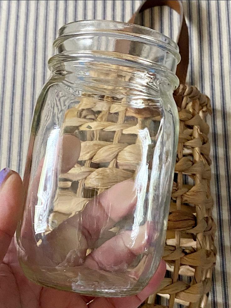 Close up of pint size mason jar going into basket.
