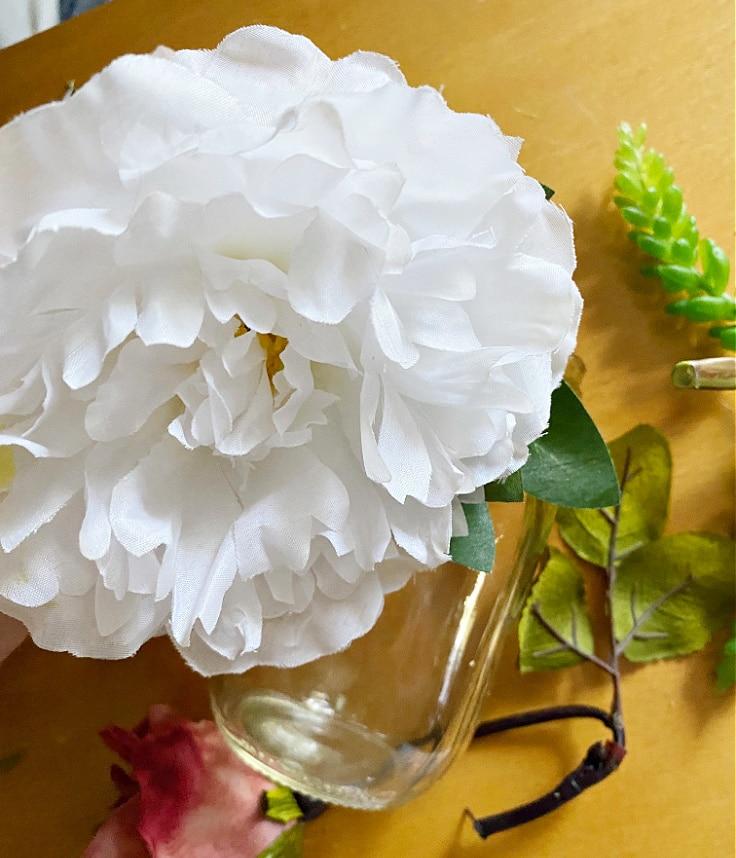 Silk flowers being placed in mason jar.