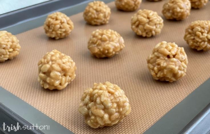 Prepared ball shaped peanut butter Rice Krispies bites on a baking sheet.