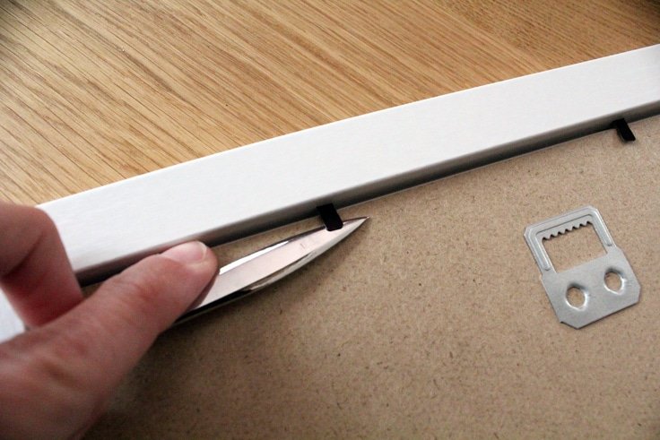 Opening the back tabs on a picture frame using a small metal letter opener.