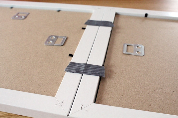 Two short pieces of gray ribbon glued to the top of two picture frames to create a hinge.
