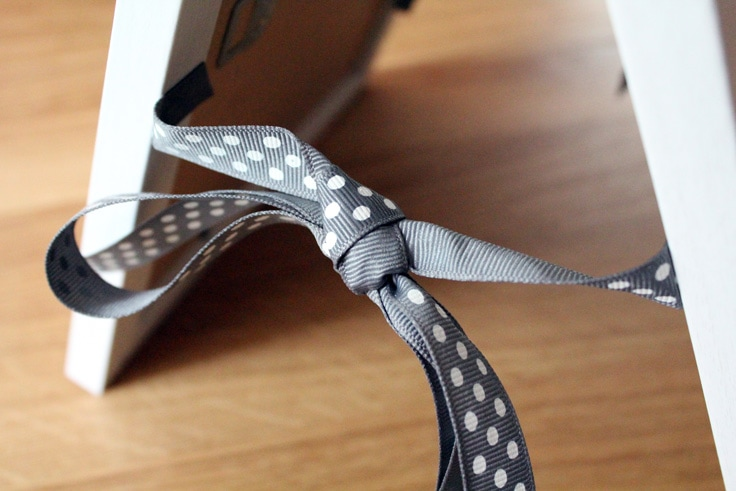 A gray ribbon with white dots holding two picture frames together in an A shape.