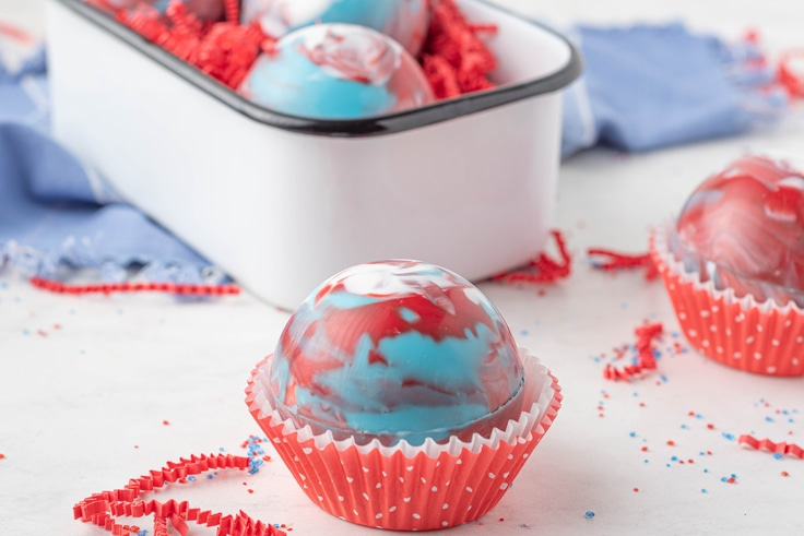 A red, white, and blue swirled cocoa ball in a paper muffin cup.