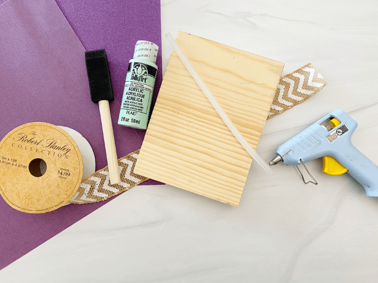 A wood block, hot glue gun, burlap ribbon, paint and a sponge brush.