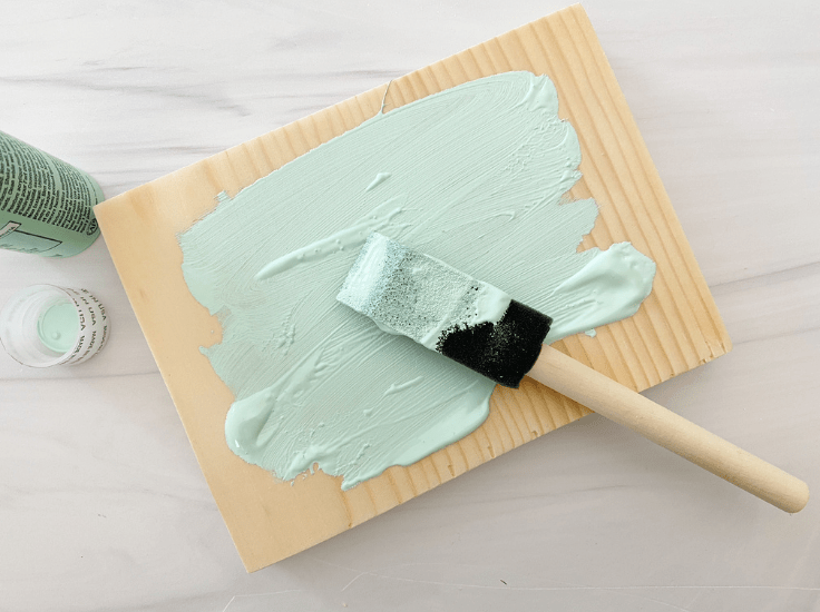 Painting a piece of wood with seafoam green paint.