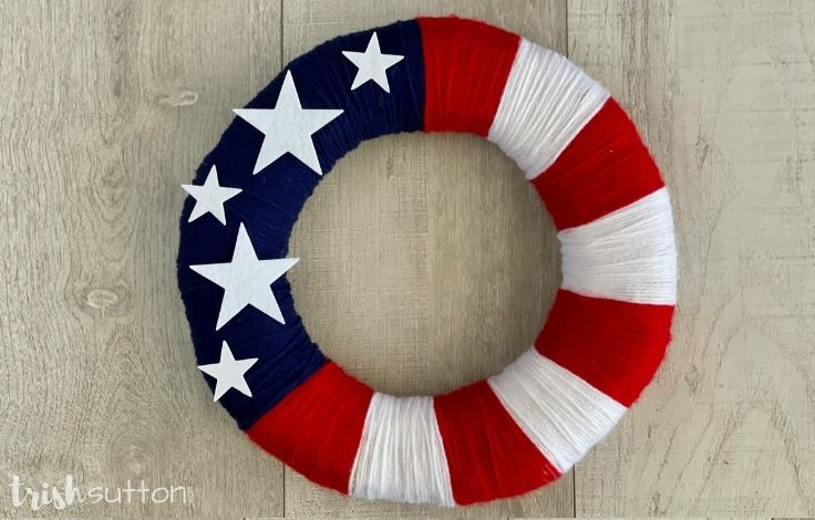 Red, white and blue DIY yarn wreath on a wood background.