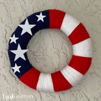 Wreath covered in stars and stripes hanging on white stucco.