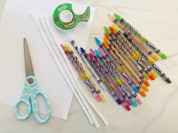 Scissors, pipe cleaners, paper, tape, and crayons