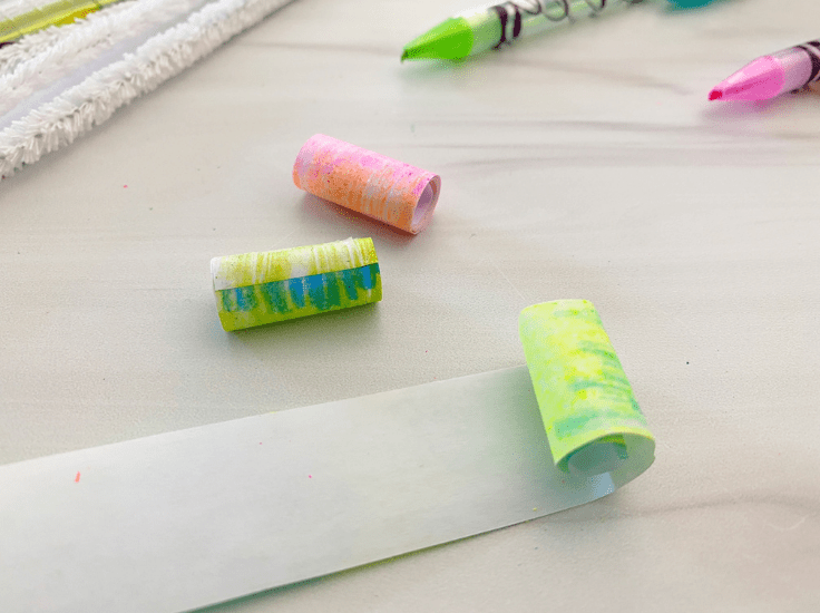 Roll each strip of colored paper up, leaving a large enough hole for the pipe cleaner to go through, and tape the edge.